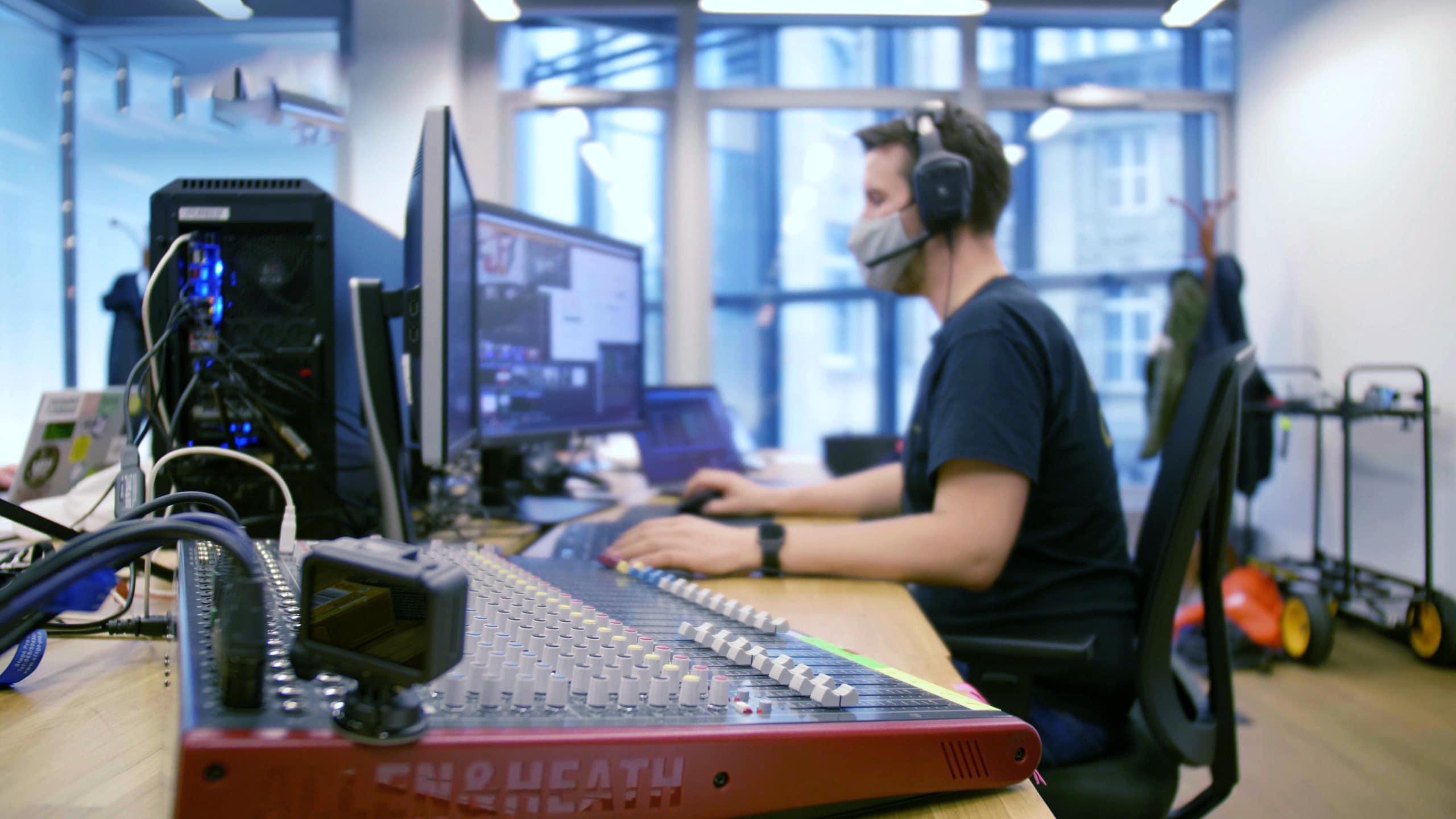 Livestreaming: Michael Neumann sitzt in einer improviesierten Regie und leitet die Livestreamproduktion Coronakonform